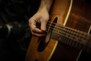 Image showing a guitarist's right hand holding a plectrum and picking individual strings in guitar lessons