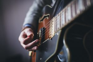 Image showing a close-up of a semi-hollow guitar with a guitarist strumming a chord in guitar lessons