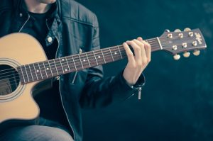 Image showing an acoustic guitarist playing notes from the G Major Scale in guitar lessons
