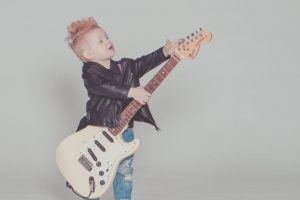 Image showing photograph of young boy holding a Fender Stratocaster electric guitar wanting guitar lessons