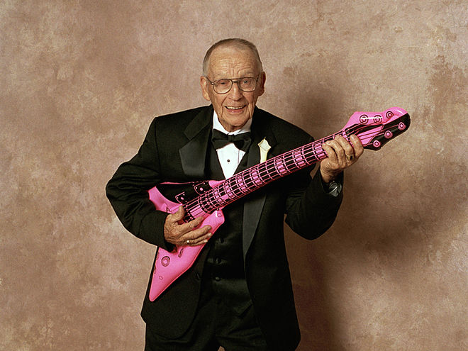 Image showing a photograph of a mature man dressed in a dinner suit holding a pink and black inflatable guitar on a page for guitar lessons