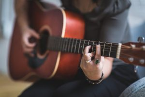 Image showing a female guitarist playing a barre chord on an acoustic guitar in guitar lessons