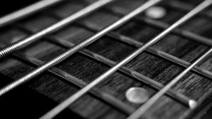 Image showing guitar strings in close up against a guitar fretboard on a page for guitar lessons