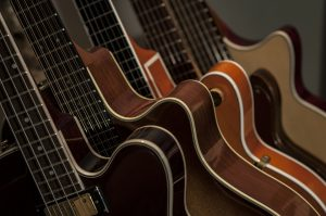 Image showing a collection of acoustic and electric guitars together on a stand